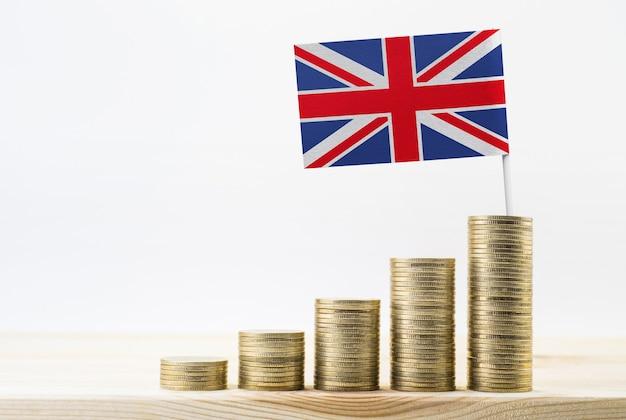 Schließen sie herauf goldmünze gestapelt, die mit flagge großbritanniens wächst