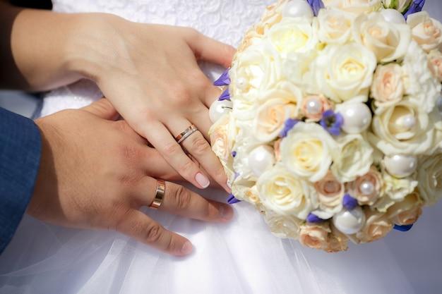 Schließen sie herauf hände der braut und des bräutigams mit hochzeitsblumenstrauß