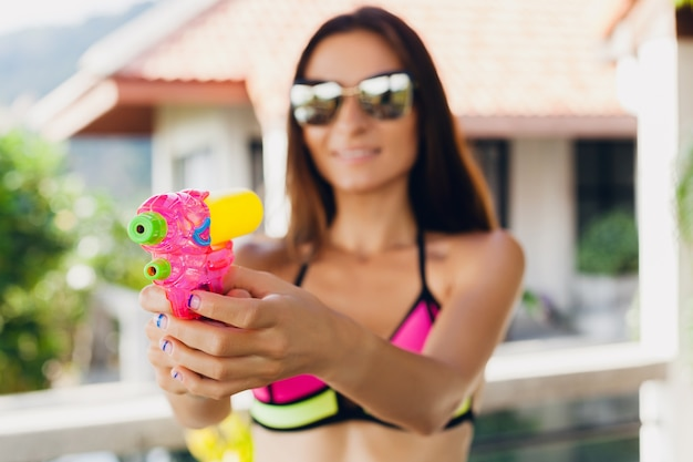 Schließen sie herauf hände der hübschen lächelnden glücklichen frau, die mit wassergewehrspielzeug am pool im tropischen sommerurlaub auf villenhotel spielt, das spaß im bikini-badeanzug, im bunten stil, in der partystimmung spielt