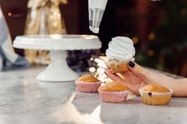 Schließen sie herauf hände der köchin mit süßwarenbeutel, der sahne auf cupcakes drückt.
