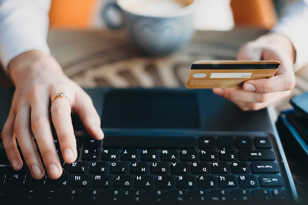 Schließen sie herauf hände, die eine plastikgoldkreditkarte halten und laptop verwenden. online-shopping-konzept.