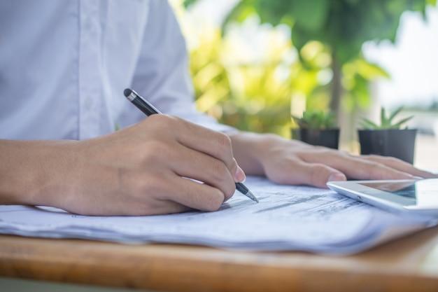 Schließen sie herauf hand, der auf papierkram von, konzeptgeschäftsfinanzierungsarbeitsjob professionelles stiftpapier witzelt
