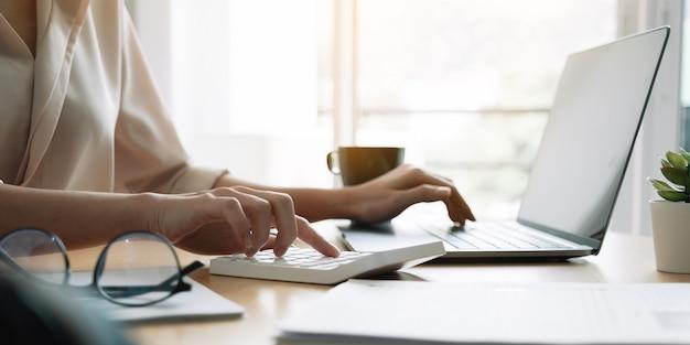 Schließen sie herauf hand der frau unter verwendung des computers, der haushaltsfinanzen oder steuern auf maschine weiblich berechnet, verwalten hausfamilienausgaben unter verwendung des taschenrechners, machen sie zahlung auf laptop