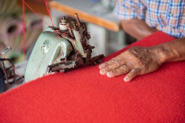 Schließen sie herauf hand des alten mannes, der einen roten teppich näht
