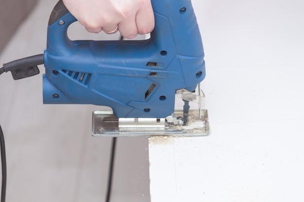 Schließen sie herauf hand des holzarbeiters oder des mannes mit elektrischer laubsäge oder stichsägewerkzeug.