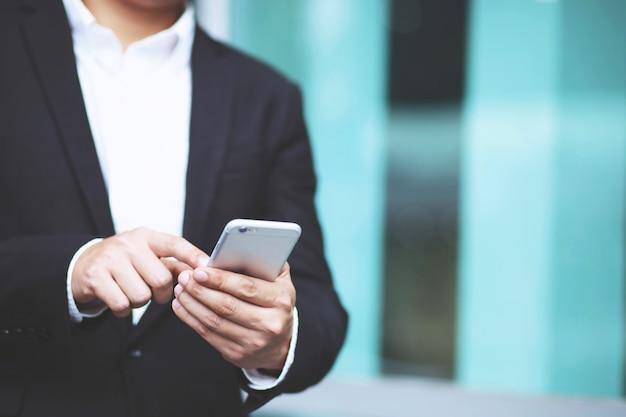 Schließen sie herauf hand des jungen mannes unter verwendung des mobilen smartphones. oder geschäftsmann kunden kontaktieren. lassen sie platz, um beschreibenden text zu schreiben.