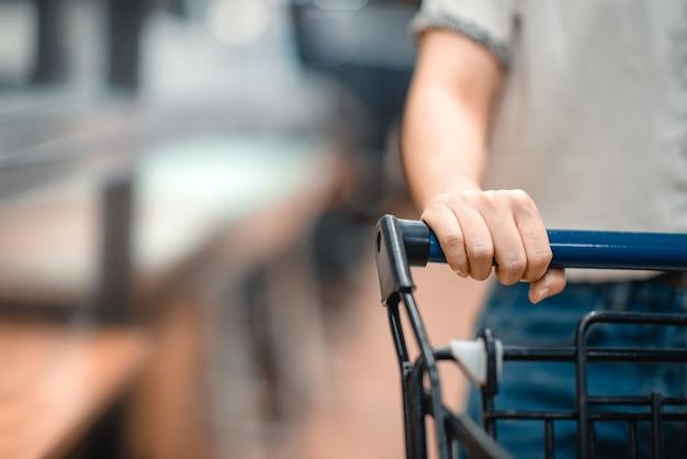 Schließen sie herauf hand des weiblichen käufers mit wagen, einkaufswagen am supermarkt.