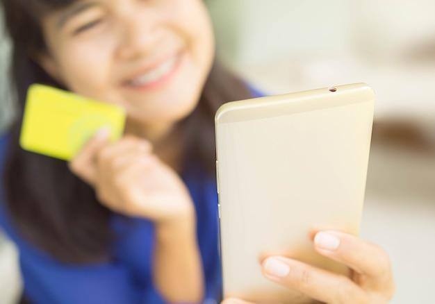 Schließen sie herauf hand, die handy mit unschärfebild der asiatischen frau hält lächeln sie glücklich, das kreditkarte auf unschärfehintergrund hält. für artikel business finance wie einkaufen nur bargeldlos.