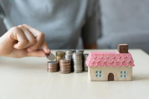 Schließen sie herauf hand, die münze, geldstapel und spielzeughaus auf tisch hält, für zukunft spart, zum erfolg führt, konzept finanziert.