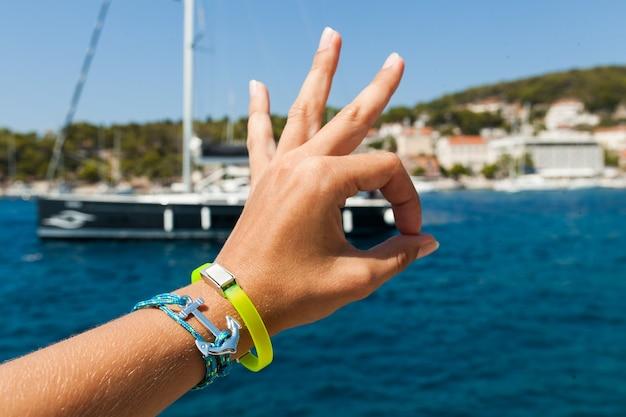 Schließen sie herauf hand, die okay zeichen am meer zeigt