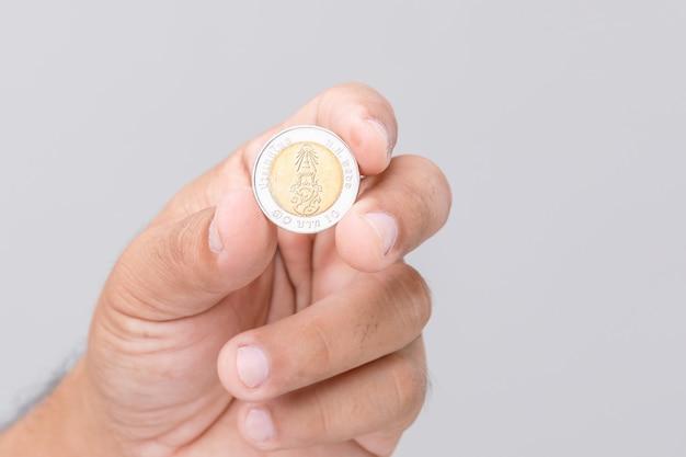 Schließen sie herauf hand, die thailand-münze (10 baht) hält.