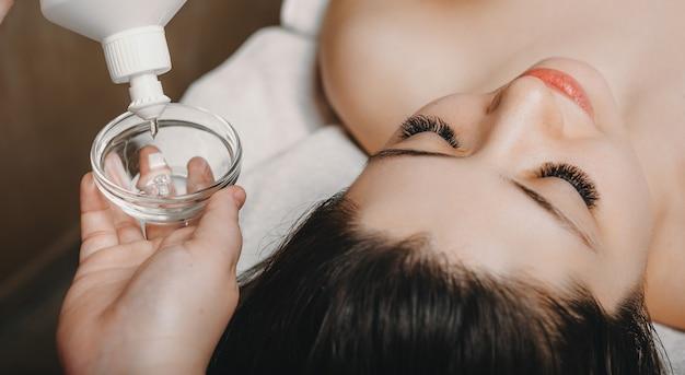 Schließen sie herauf hand einer weiblichen kosmetikerin unter verwendung einer transparenten maske aus einer flasche, um auf ein weibliches gesicht für hautpflegebehandlung aufzutragen.