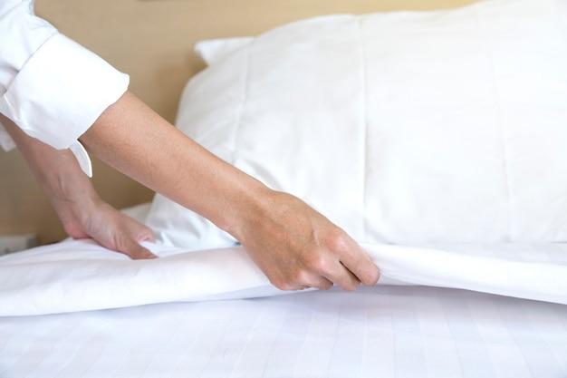 Schließen sie herauf hand gründete weißes bettlaken im hotelzimmer