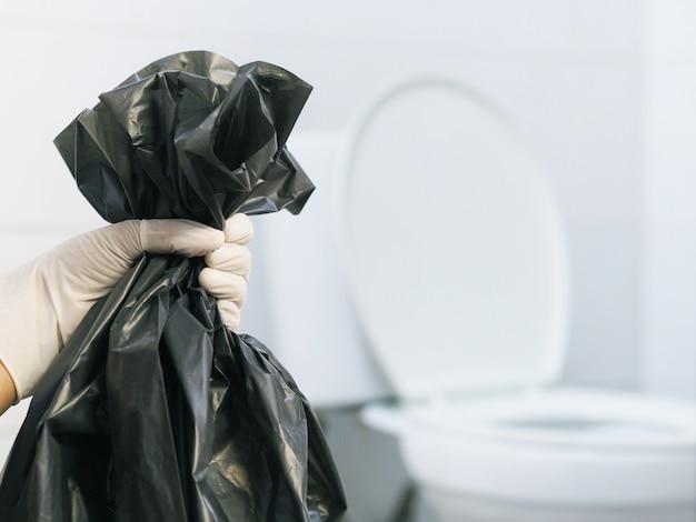 Schließen sie herauf hand mit handschuh, der schwarzen müllsack über verschwommener weißer toilette hält