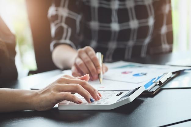 Schließen sie herauf handfrau, die finanzen tut und berechnen sie auf dem schreibtisch über kosten im büro.