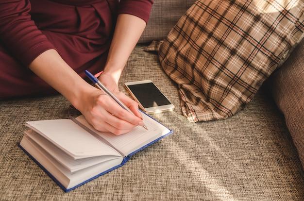 Schließen sie herauf handfrauenschreiben in ihrem notizbuch