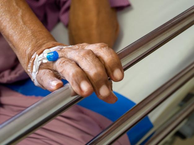 Schließen sie herauf handpatient-ältere mannhand mit intravenöser (iv) lösung der salzlösung im krankenhaus.