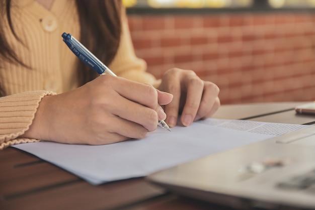 Schließen sie herauf handschrift auf dokumentgeschäftsfrauen, die von zu hause aus arbeiten