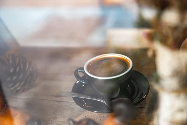 Schließen sie herauf heißen schwarzen kaffee in der schwarzen schale auf holztisch, durch fensteransicht