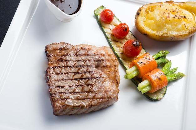 Schließen sie herauf hida-rindfleischsteak mit gegrillter tomate, karotte, gurke und spargel auf weißer platte