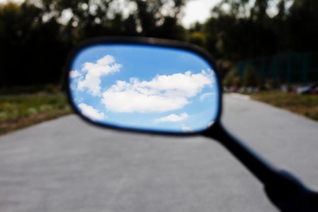 Schließen sie herauf himmel im motorradspiegel