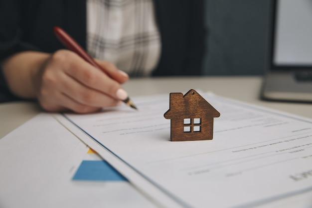 Schließen sie herauf holzspielzeughaus mit frau unterzeichnet einen kaufvertrag oder eine hypothek für ein haus, immobilienkonzept.