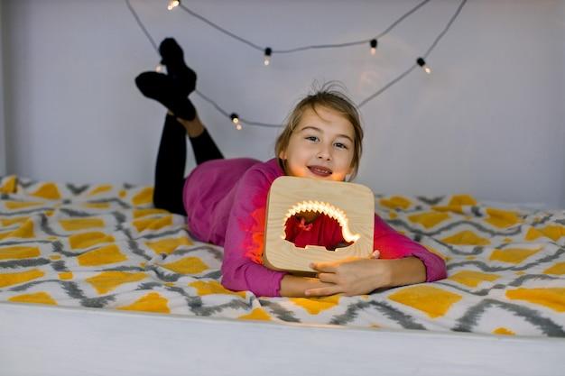 Schließen sie herauf horizontale aufnahme des glücklichen lächelnden 10-jährigen mädchens, das auf gemütlichem bett liegt und schöne hölzerne nachtlampe mit igelbild hält.