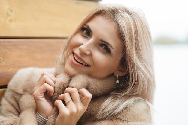 Schließen sie herauf hübsche blonde frau mit blauen augen im pelzmantel 30 alter auf holzwand. luxus-lifestyle-shopping