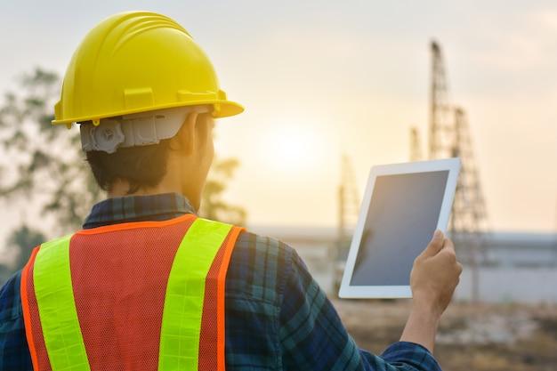 Schließen sie herauf ingenieurbau, der tablett hält, das arbeitseigentumstechnologie prüft