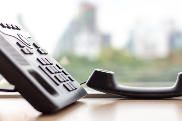 Schließen sie herauf ip-telefon für schreibtisch des büros auf dem tisch mit fensterstadtansicht