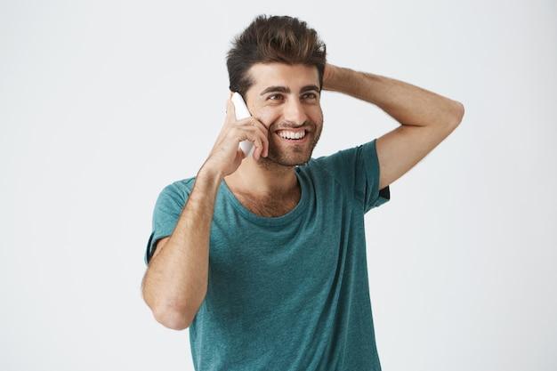 Schließen sie herauf isoliertes porträt des lächelnden spanischen mannes im trendigen t-shirt, lächelnd und seinen kopf haltend, während am telefon mit bestem freund sprechen.