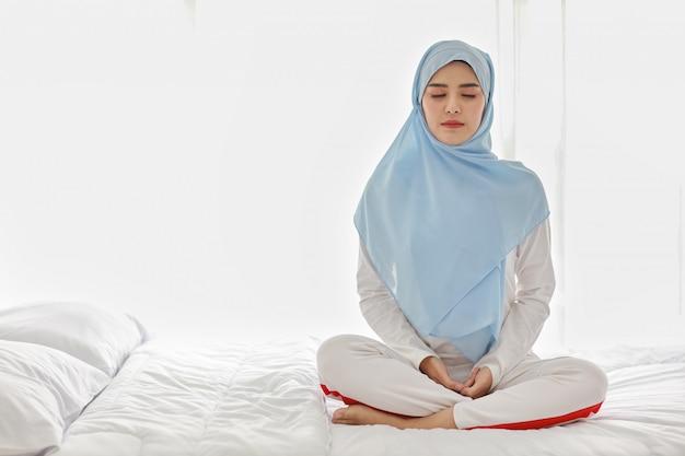 Schließen sie herauf junge asiatische muslimische frau, die auf bett sitzt und meditation genießt. schöne frau in nachtwäsche mit blauem hijab praktiziert yoga im schlafzimmer mit frieden und ruhe. gesundes und lifestyle-konzept