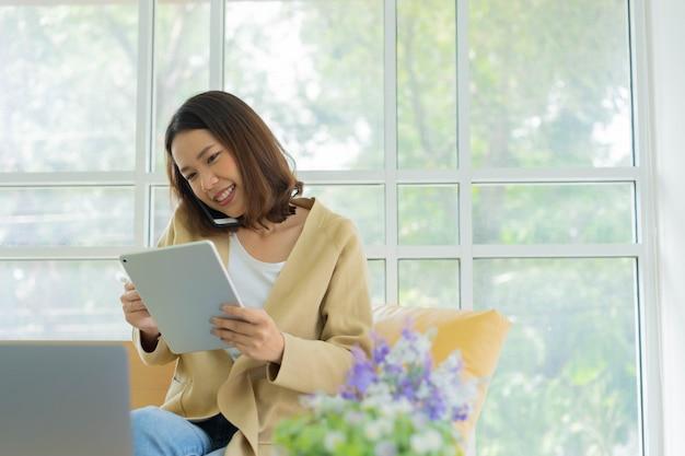 Schließen sie herauf junge geschäftsfrauenanruf am telefon mit der überprüfung der arbeit auf tablet und laptop zu hause