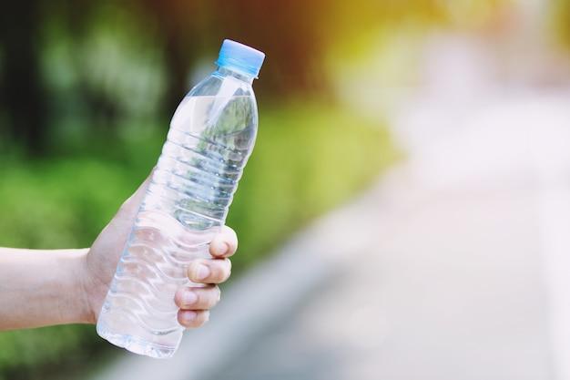Schließen sie herauf junge hand, die frische trinkwasserflasche von einem plastik im park hält.
