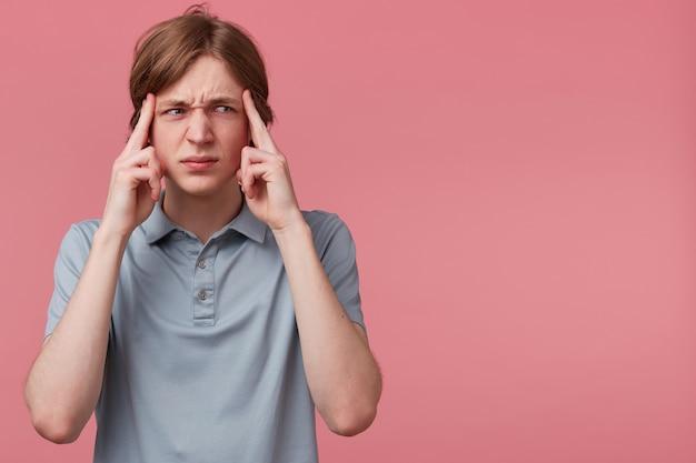 Schließen sie herauf junger mann, der denkt, sich bemüht, sich an etwas zu erinnern, das auf der rechten seite auf leerem copyspace fokussiert aussieht, finger auf schläfen isolierten rosa hintergrund. gesichtsausdrücke mit negativen emotionen