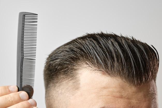 Schließen sie herauf junger mann, der seine haare mit einem plastikkamm kämmt. haarstyling nach dem friseursalon.