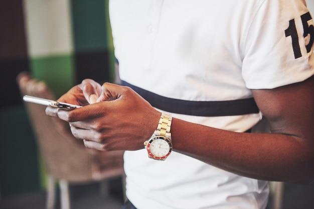 Schließen sie herauf junger mann, der smartphone im café betrachtet