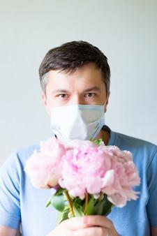 Schließen sie herauf junger mann in der medizinischen maske, die blumen hält. mann in einer medizinischen antivirenmaske hält einen blumenstrauß. erholung von coronavirus. stoppen sie die covid-19-pandemie