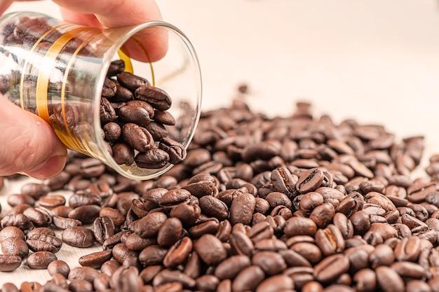 Schließen sie herauf kaffee auf hölzernem hintergrund des schmutzes. die hand eines mannes ruft kaffee aus einer glastasse auf den tisch. auswahl der besten kaffeebohnen.