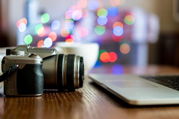 Schließen sie herauf kamera auf dem tisch des fotografarbeitsplatzes mit laptop