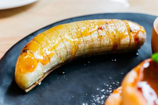 Schließen sie herauf karamellbanane für das essen mit flaumigen pfannkuchen und eiscreme.