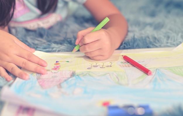 Schließen sie herauf kind zeichnen und malen von ihrer familie zu hause für grußkarte erstellen