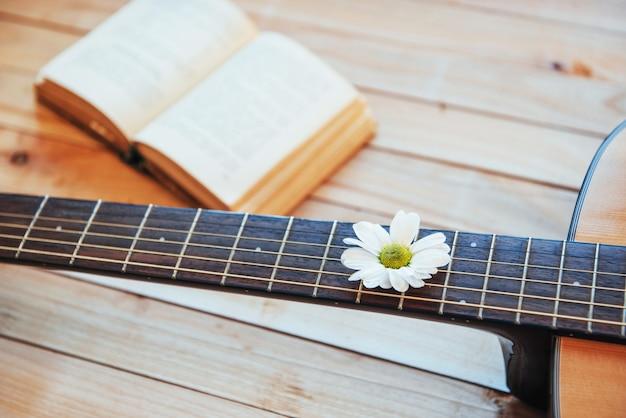 Schließen sie herauf kopf der klassischen gitarre mit gläsern und buch