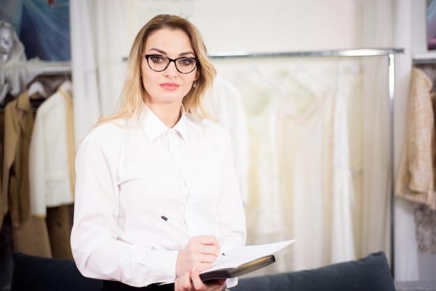 Schließen sie herauf kopfschussporträt des lächelnden erfolgreichen kaukasischen frau-modedesigners oder der schneiderpose im büro.