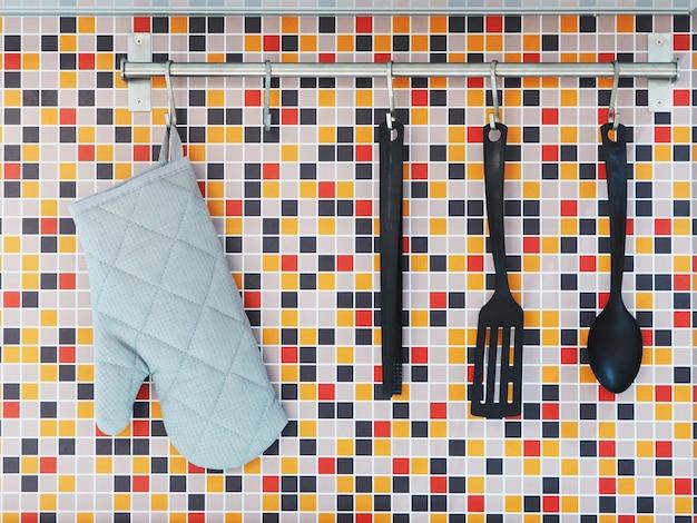 Schließen sie herauf küchenutensilien, die über bunten mosaikwandfliesen hängen.