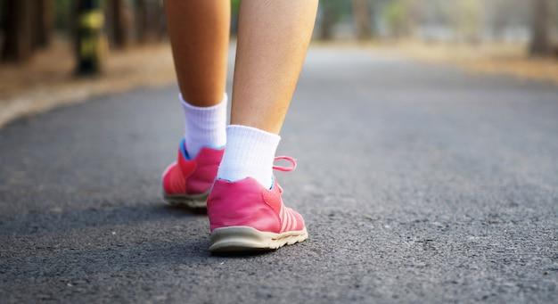 Schließen sie herauf läuferfrauenfüße auf straße am park