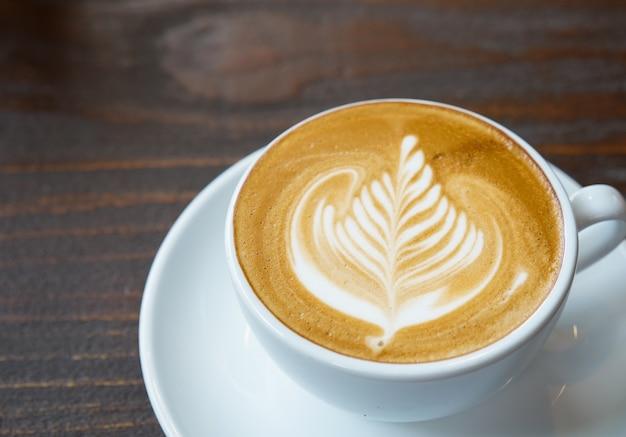 Schließen sie herauf lattekunstkaffee auf hölzernem hintergrund, getränkekonzept.