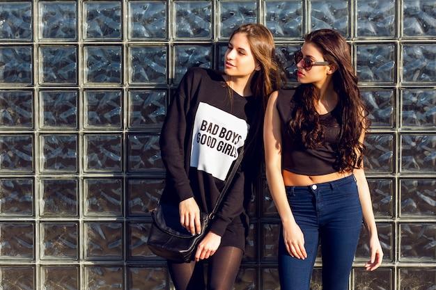 Schließen sie herauf lebensstil-porträt von zwei hübschen jungen frauen, die gegen glasstadtwand am sonnigen tag aufwerfen. trägt ein schwarzes top, einen pullover und eine lederjacke.