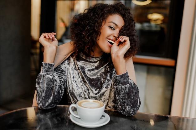 Schließen sie herauf lebensstilporträt der glücklichen sorglosen schwarzen frau, die kaffeepause in paris genießt.