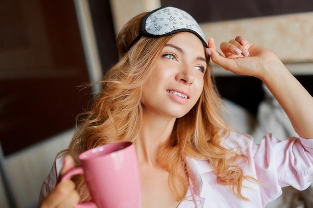Schließen sie herauf lebensstilporträt der glückseligen frau mit offenem lächeln, das in augenmaske zu hause aufwirft und heißen tee trinkt.